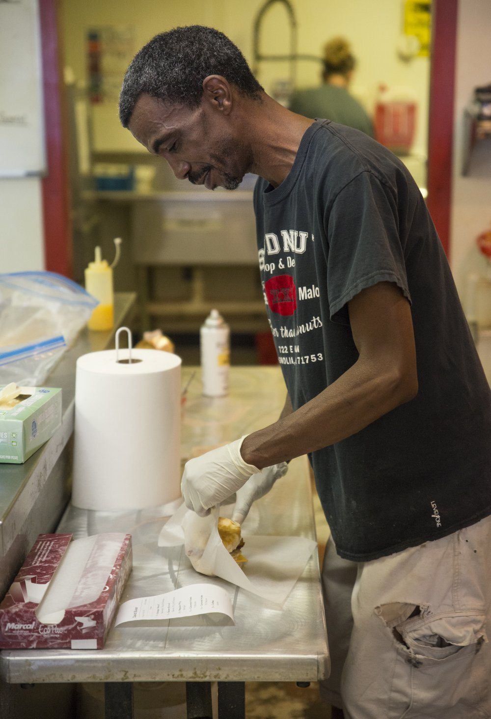 Spudnut Shop employee Tracy Jones wraps a sausage biscuit on the restaurant's final day of business.