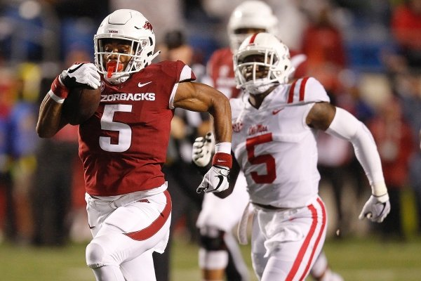 Arkansas running back Rakeem Boyd (left) races to the end zone for a 69-yard touchdown during the first quarter on Saturday, Oct. 13, 2018, at War Memorial Stadium in Little Rock.