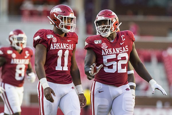 Arkansas defensive end Mataio Soli (11) listens as defensive tackle T.J. Smith (52) talks during a game against Portland State on Saturday, Aug. 31, 2019, in Fayetteville.