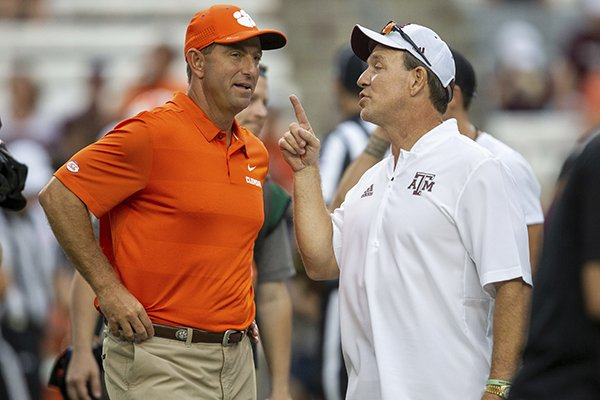 Clemson head coach Dabo Swinney and Texas A&M head coach Jimbo Fisher talk before the start of an NCAA college football game Saturday, Sept. 8, 2018, in College Station, Texas. (AP Photo/Sam Craft)