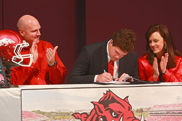 Pulaski Academy's tight end Hunter Henry sign a letter of intent to play football at Arkansas during a ceremony at the school Wednesday, Feb. 6, 2013, in Little Rock. At left is his father Mark Henry and right is his mother Jenny Henry.
