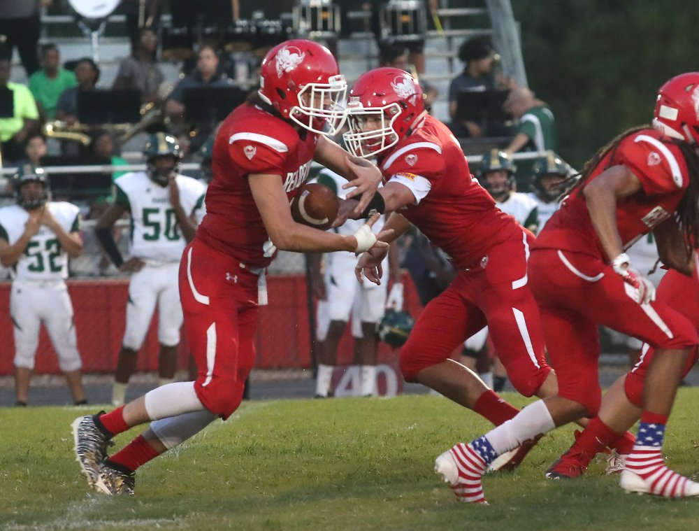 The Sentinel-Record/Richard Rasmussen SMOOTH TRANSITION: Mountain Pine's Jace Chancon, left, takes a handoff from quarterback Collin Smith while facing Mineral Springs Friday night in Mountain Pine.