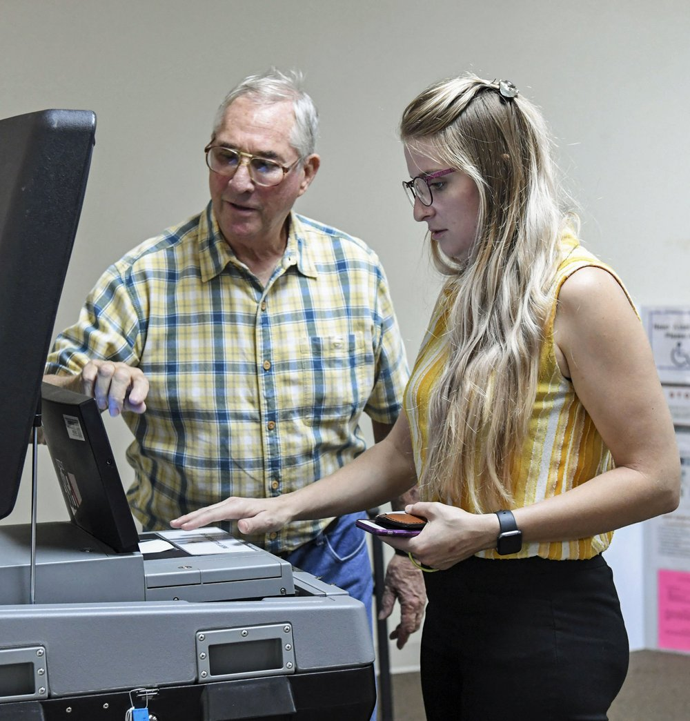 Ira Roseberry, left, helps voter Jaylene Gonsalves enter her ballot into an electronic counter at the Garland County Election Commission on Tuesday. - Photo by Grace Brown of The Sentinel-Record