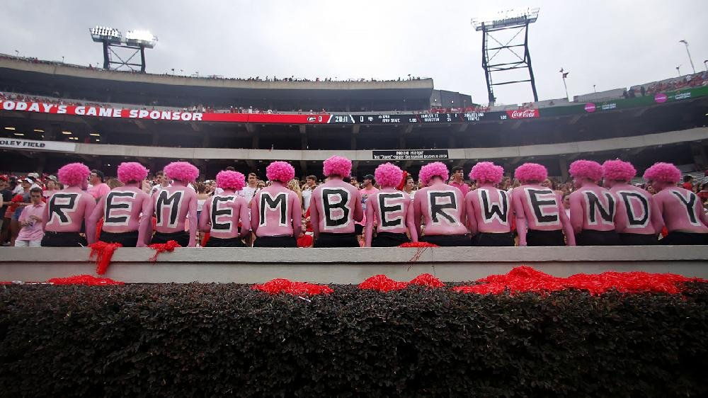 Georgia students observe a moment of silence in honor of Wendy Anderson, the wife of Arkansas State Coach Blake Anderson, before the game between the Bulldogs and Red Wolves on Saturday at Athens, Ga. Wendy Anderson died in August after a battle with breast cancer. See more photos at arkansasonline.com/915pinkout.
