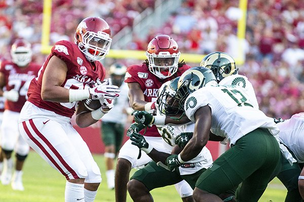 Arkansas tight end C.J. O'Grady (left) pulls away from several Colorado State defenders during a game Saturday, Sept. 14, 2019, in Fayetteville. O'Grady broke away from five tacklers on the play that resulted in a 62-yard touchdown.