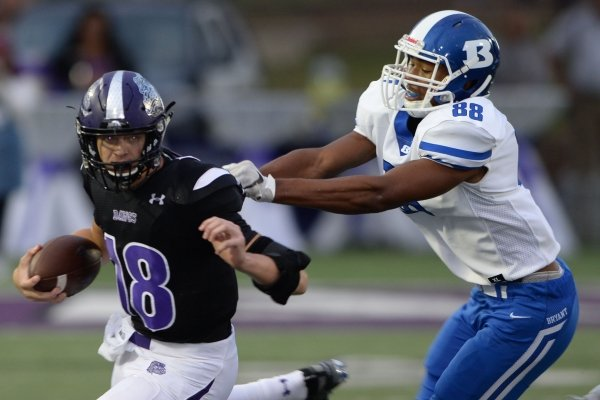 Fayetteville quarterback Hank Gibbs (18) looks for a receiver Friday, Sept. 20, 2019, as he is pressured by Bryant linebacker Catrell Wallace (88) during the first half of play at Harmon Stadium in Fayetteville. Visit nwadg.com/photos to see more photos from the game.