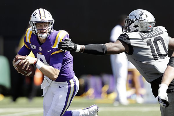 LSU quarterback Joe Burrow, left, scrambles away from Vanderbilt defensive lineman Dayo Odeyingbo (10) in the first half of an NCAA college football game Saturday, Sept. 21, 2019, in Nashville, Tenn. (AP Photo/Mark Humphrey)