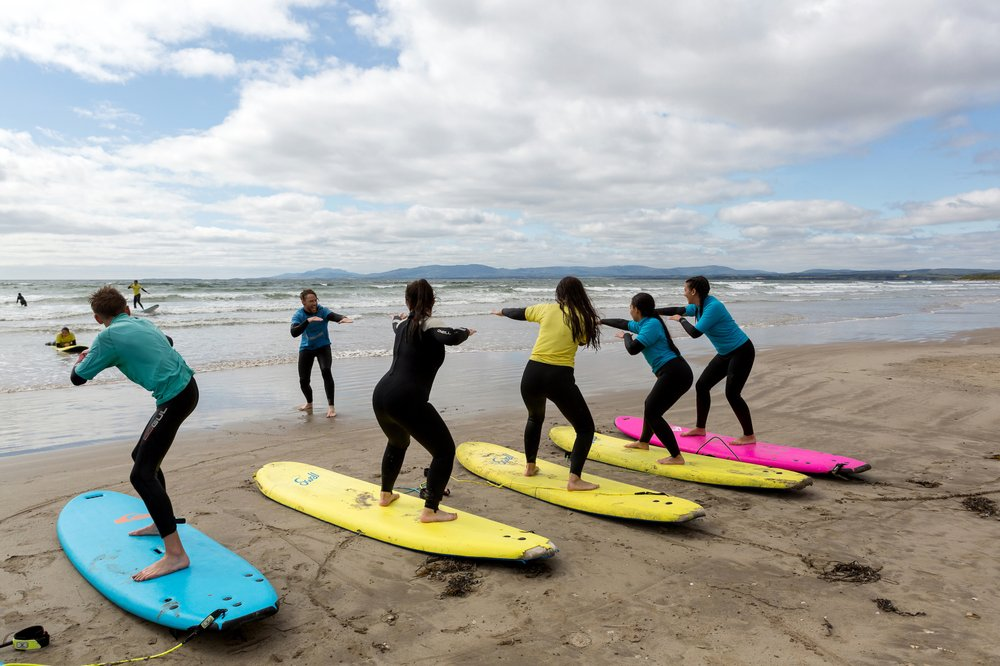 New surfers learn techniques in a surfing class at Rossnowlagh, Ireland. The long sandy beach there is a popular spot for beginner and intermediate surfers. (Photo by Therese Aherne via The New York Times)