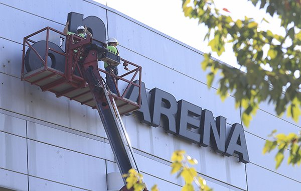 Eddie Ashley (left) and Tyler Brazil with Arkansas Sign and Neon remove Verizon signage Monday from Verizon Arena in North Little Rock. The facility will change to Simmons Bank Arena this week, nearly a year after the bank signed a multi-million dollar deal to acquire naming rights.