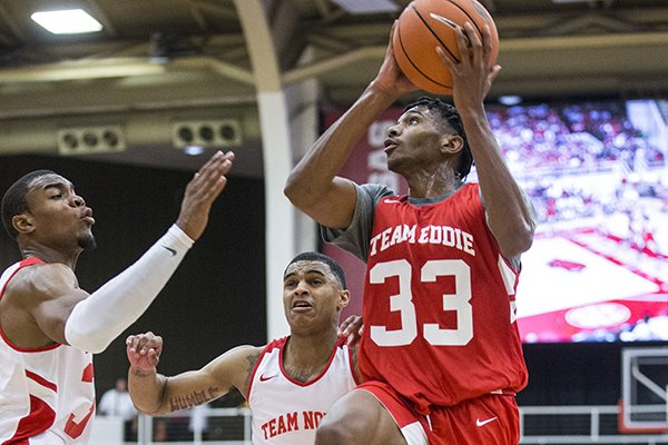 Arkansas guard Jimmy Whitt (33) shoots as Reggie Chaney (35) and Jalen Harris (5) guard during the Razorbacks' Red-White Game on Saturday, Oct. 5, 2019, in Fayetteville.
