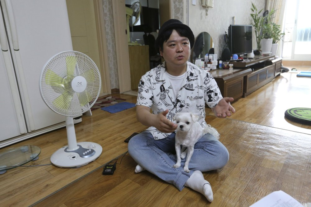 Jang Myung-jin holds his dog while talking about his YouTube channel at home in Seoul in this July photo. speaks during an interview at his house in Seoul, South Korea. Jang enjoys putting on funny wigs and hamming it up on his channel. (Photo by Ahn Young-Joon via AP)