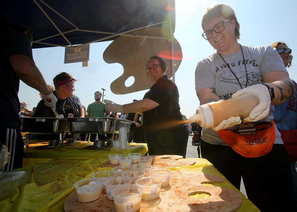 Jera Cobb (right), with the B A Burrito team from Jonesboro puts seasoning on cheese dip at the ninth Annual World Championship Cheese Dip Championship on Saturday at the Clinton Presidential Center in Little Rock. The team won the award for best booth. Arkansas Democrat-Gazette/Thomas Metthe