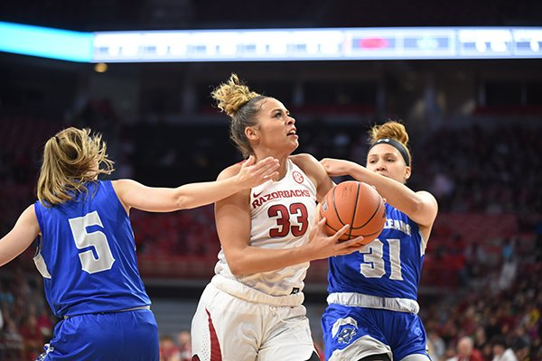 Arkansas' Chelsea Dungee (33) goes up for a shot at New Orleans' Asia Woods (31) and Traya Bruce (5) defend during a game Friday, Nov. 8, 2019, in Fayetteville.