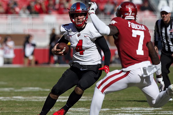 Western Kentucky quarterback Ty Storey (4) runs with the ball as Arkansas defensive back Joe Foucha (7) pursues during a game Saturday, Nov. 9, 2019, in Fayetteville.