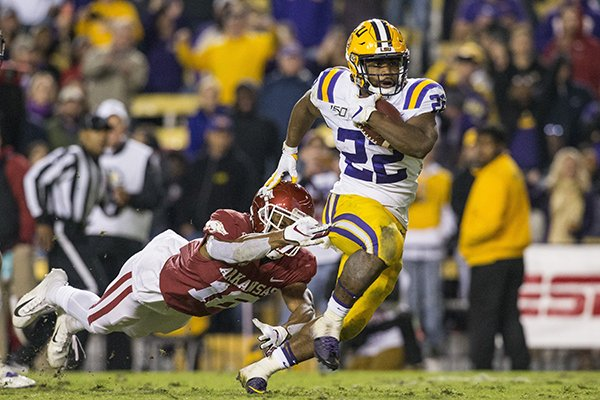 LSU running back Clyde Edwards-Helaire breaks a tackle attempt by Arkansas safety Myles Mason on his way to a touchdown during the third quarter of a game Saturday, Nov. 23, 2019, in Baton Rouge, La.