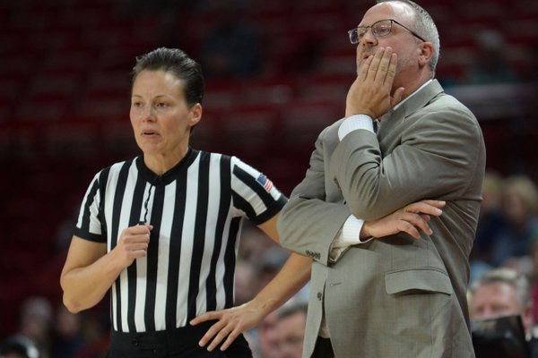 Arkansas coach Mike Neighbors speaks Thursday, Nov. 14, 2019, with a game official during the second half of play against Oral Roberts in Bud Walton Arena.