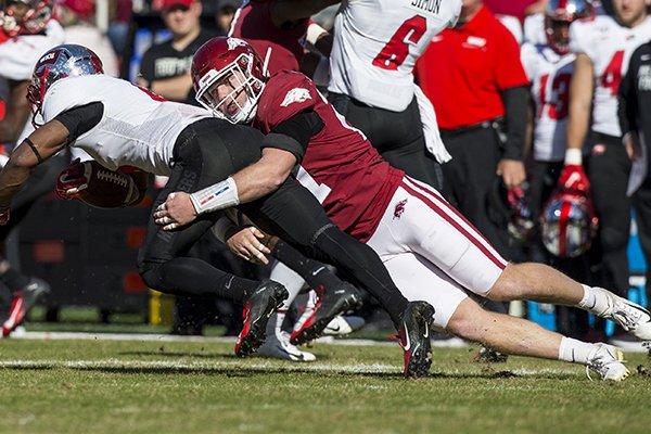 Arkansas linebacker Hayden Henry tackles Western Kentucky running back Gaej Walker during a game Saturday, Nov. 9, 2019, in Fayetteville.