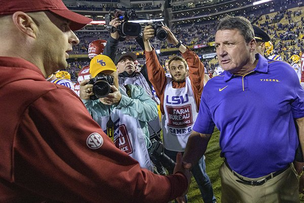 LSU coach Ed Orgeron, right, greets Arkansas coach Barry Lunney Jr. after LSU's 56-20 victory in a game in Baton Rouge, La., Saturday, Nov. 23, 2019. (AP Photo/Matthew Hinton)