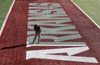 """Josh Oliver with the Arkansas Department of Parks and Tourism sprays white paint to highlight the word """"Arkansas"""" in the west end zone of War Memorial Stadium in Little Rock on Wednesday, Nov. 27, 2019."""