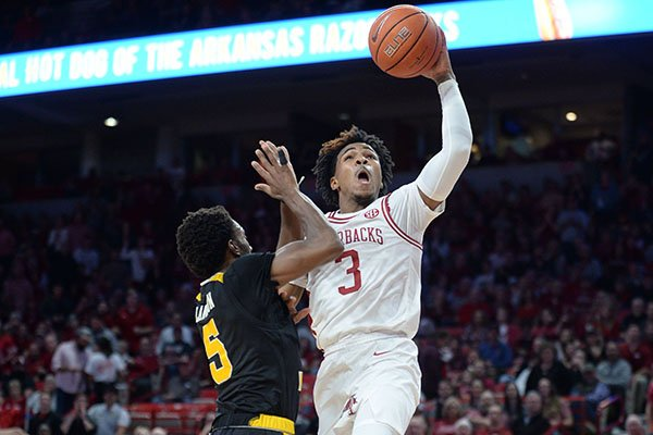 Arkansas guard Desi Sills (3) reaches to score Saturday, Nov. 30, 2019, as he is fouled by Northern Kentucky Bryson Langdon during the first half of play in Bud Walton Arena.