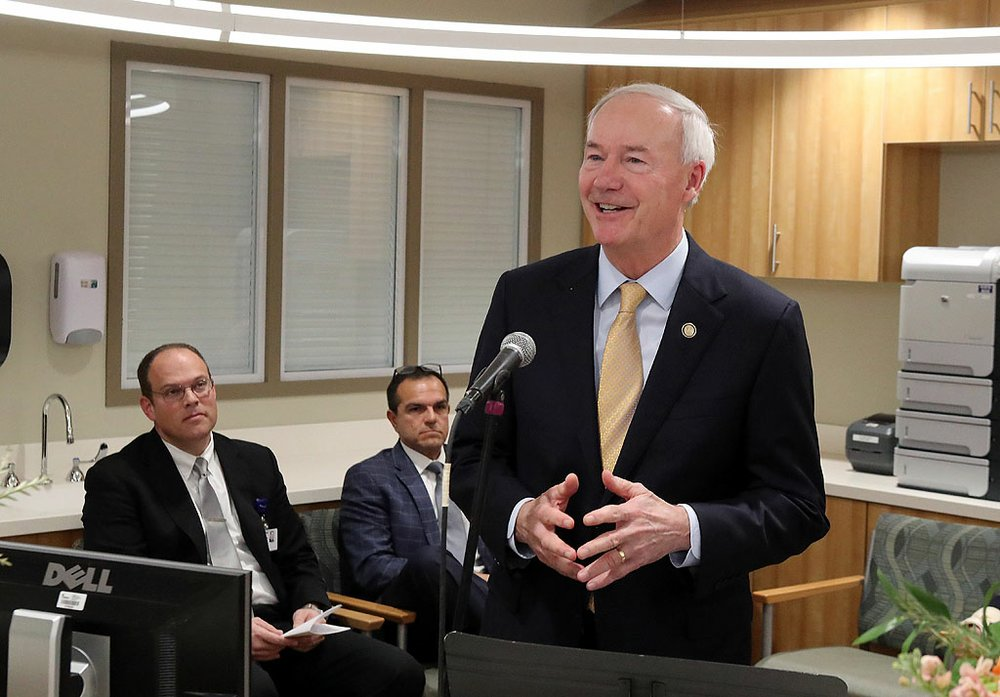 Gov. Asa Hutchinson, right, speaks as CHI St. Vincent Hot Springs President Dr. Doug Ross, left, and Dr. Jamie Cardenas listen during the grand opening for the new CHI St. Vincent Hot Springs Anthony Childbirth Center on Monday. - Photo by Richard Rasmussen of The Sentinel-Record