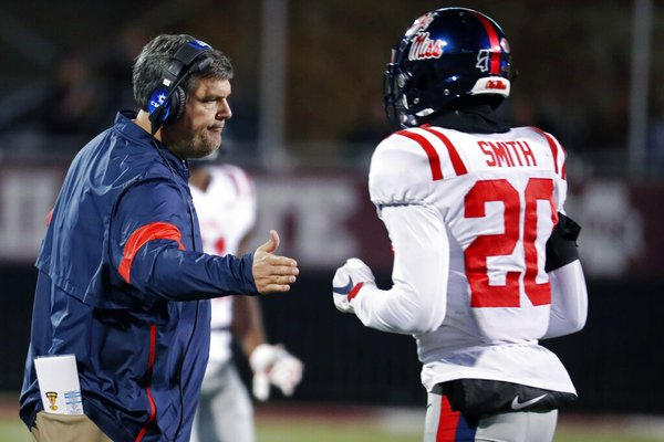 """In this Nov. 28, 2019 photo, Mississippi head coach Matt Luke reaches out to Mississippi defensive back Keidron Smith (20) following a second half play during an NCAA college football game against Mississippi State, in Starkville, Miss. Mississippi has fired Luke, three days after his third non-winning season ended with an excruciating rivalry game loss. Athletic director Keith Carter said Sunday, Dec. 1, 2019 the decision to change coaches was made after evaluating the trajectory of the program and not seeing enough """"momentum on the field. (AP Photo/Rogelio V. Solis)"""
