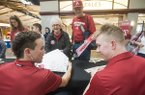 Pamela Short and husband David Short of Grapevine, Texas, (grandparents of Arkansas pitcher Kole Ramage), get autographs from infielder Coby Boulware (left) and outfieder Heston Kjerstad Saturday, Feb. 9, 2019, during Arkansas baseball's annual Meet the Razorbacks Day at Northwest Arkansas Mall in Fayetteville.
