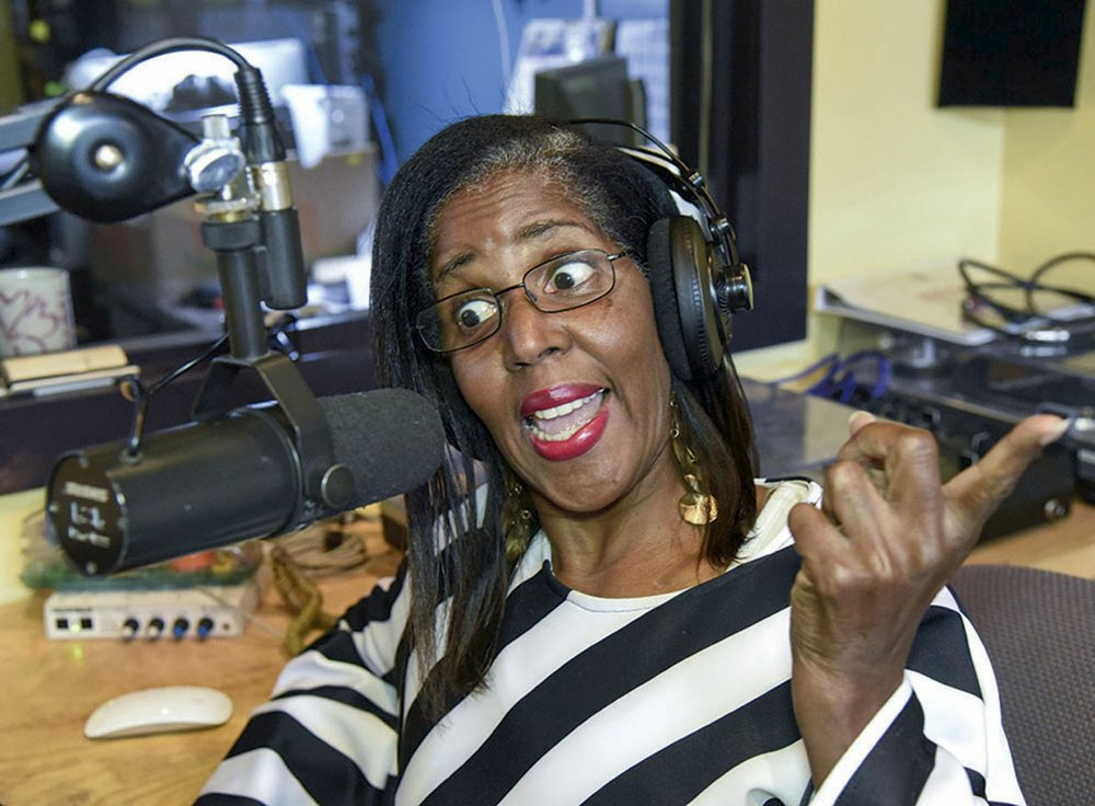 Pier Clark, known for her on-air personality, Mama P, demonstrates a segment of her show at KUHS Community Radio Station. - Photo by Grace Brown of the Sentinel-Record.