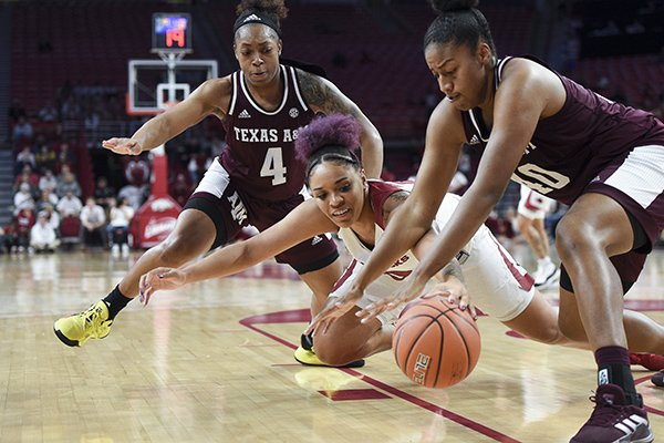 Arkansas forward Kiara Williams (10) and Texas A&M center Ciera Johnson (40) dive for a loose ball during a game Thursday, Jan. 2, 2020, in Fayetteville.