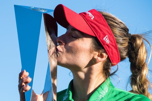 Gaby Lopez kisses the trophy after winning the Tournament of Champions LPGA golf tournament, Monday, Jan. 20, 2020, in Lake Buena Vista, Fla. Lopez ran in a 30-foot putt for birdie, to defeat Nasa Hataoka in a seven-hole playoff that took an extra day to finish after play was halted Sunday because of darkness. (Michael Johnson/Daily Sun via AP)