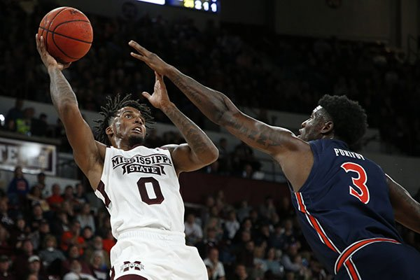 Mississippi State guard Nick Weatherspoon (0) attempts to shoot over the outstretched arm of Auburn forward Danjel Purifoy (3) during the first half of an NCAA college basketball game, Saturday, Jan. 4, 2020 in Starkville, Miss. Auburn won 80-68. (AP Photo/Rogelio V. Solis)