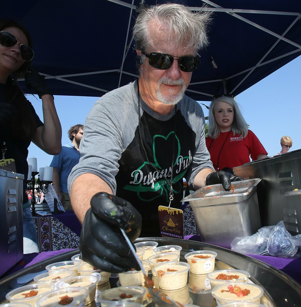 Don Dugan of Dugan's Pub and Dizzy's Gypsy Bistro, serves cheese dip at the Ninth Annual World Championship Cheese Dip Championship in October. Dugan and his wife, Tasha Stratton, will be taking over South on Main in February from departing owner-chef Matt Bell and his wife Amy.  (Democrat-Gazette file photo/Thomas Metthe)