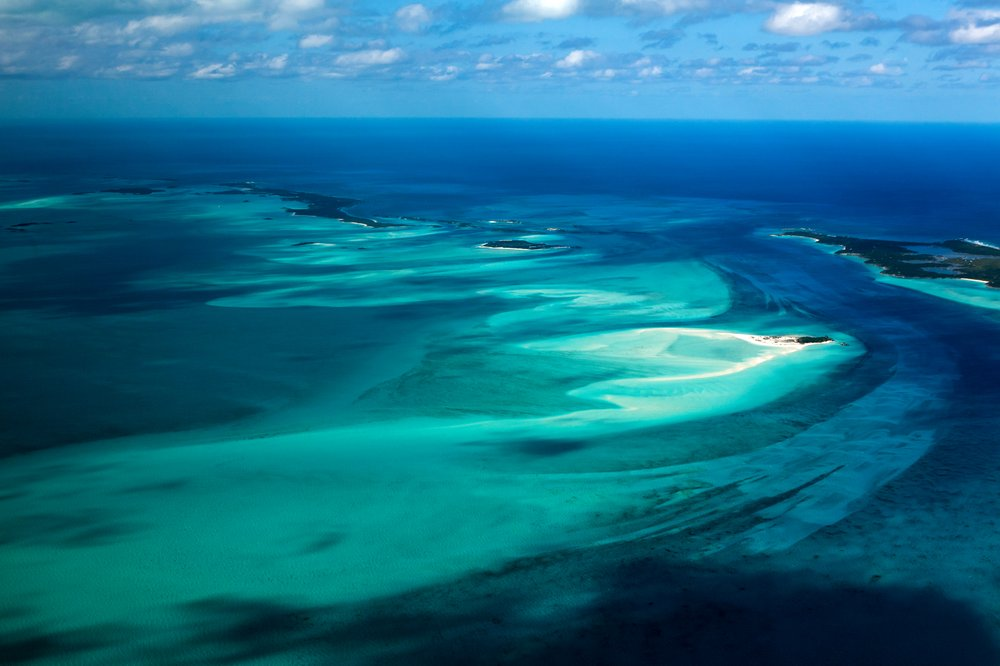 The Bahamas' Exuma Islands are surrounded by brilliant blue ocean waters. The shallow waters prevent an influx of cruise ships to this more remote area. (The New York Times/Sara Fox)