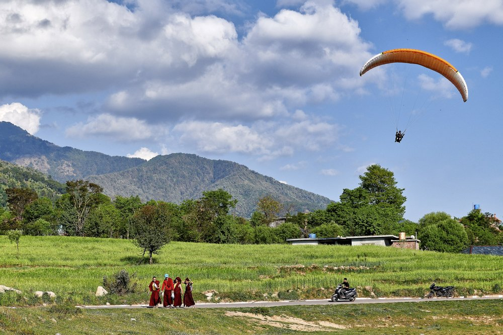 Monks walk near a paraglider landing site at Bir in Himachal Pradesh, India, where the scenery makes the high-flying activity very popular. (The New York Times/Poras Chaudhary)