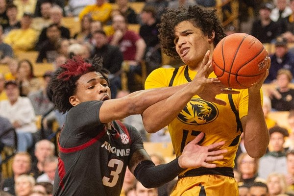 Missouri's Dru Smith, right, is fouled by Arkansas' Desi Sills, left, during the first half of an NCAA college basketball game Saturday, Feb. 8, 2020, in Columbia, Mo. (AP Photo/L.G. Patterson)
