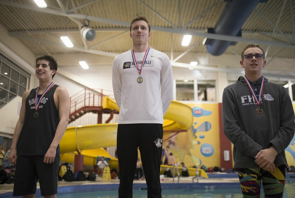 Bentonville senior Ryan Husband medals first in the boys 200 yard individual medley with Springdale's Kevin Brumfield (left) placing second and Fayetteville's Jackson Woodard (right) placing third, Thursday, February 13, 2020 during the 6A-West Conference swim meet at the Jones Center in Springdale. Check out nwaonline.com/200214Daily/ for today's photo gallery. (NWA Democrat-Gazette/Charlie Kaijo)