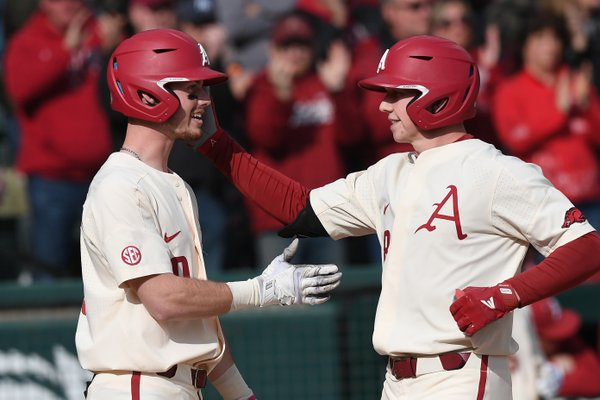 Heston Kjerstad celebrates with teammate Matt Goodheart (10) after one of Kjerstad's home runs during the Razorbacks 12-3 victory over Eastern Illinois on Sunday, February 16, 2020 at Baum-Walker Stadium.