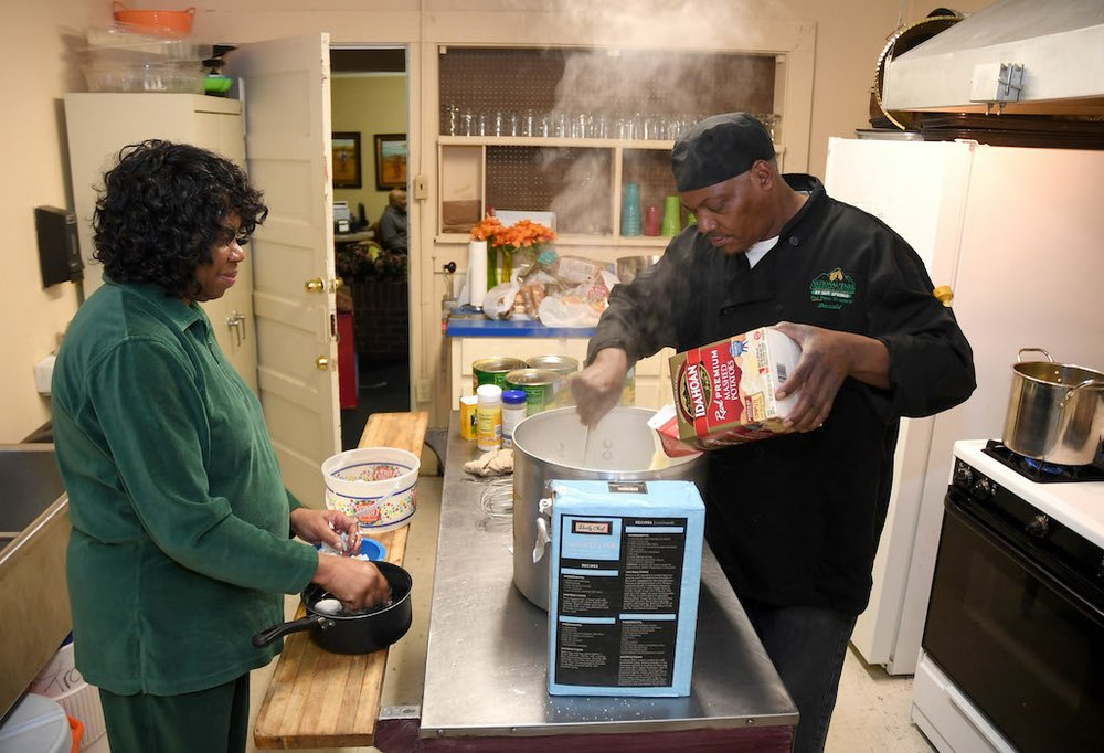 Linda Franklin and Donald Giles prepare food at the Webb Community Center for a Christmas Eve dinner in 2016. - File photo by The Sentinel-Record