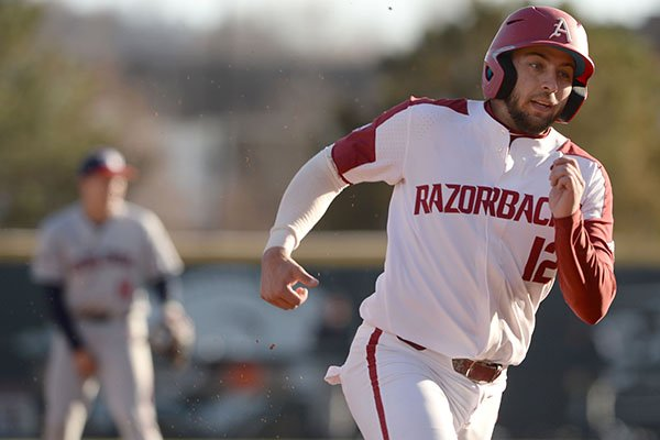 Arkansas catcher Casey Opitz heads to third base Friday, Feb. 21, 2020, on his way to the plate on a single by Robert Moore during the fifth inning at Baum-Walker Stadium in Fayetteville.