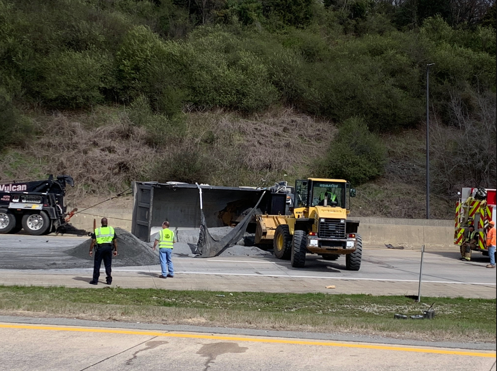 First responders work at the scene of a commercial truck rollover on Interstate 40 near the Interstate 30 interchange in Pulaski County on Monday.
