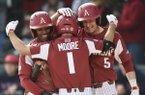 Arkansas outfielder Christian Franklin (25) and infielder Jacob Nesbit (5) react as infielder Robert Moore (1) runs home for a score Saturday at Baum-Walker Stadium in Fayetteville.