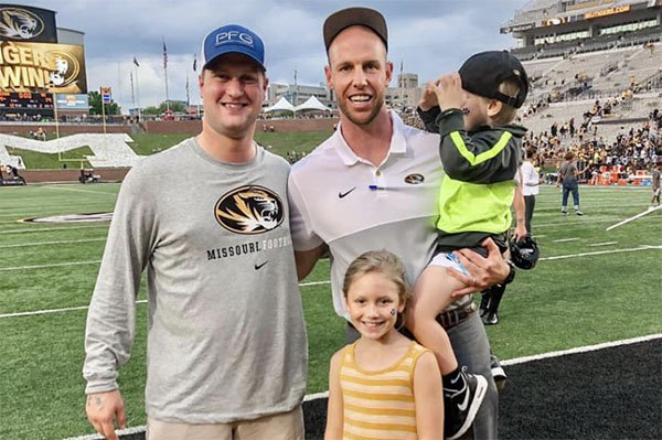 Travis Gipson (left) is shown with Joseph Henry and Henry's children Ford and Linley following a football game in Columbia, Mo.