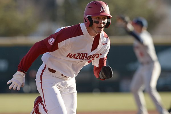 Arkansas first baseman Cole Austin heads to third base Friday, Feb. 21, 2020, on an RBI slash-bunt single by Robert Moore during the fifth inning at Baum-Walker Stadium in Fayetteville.