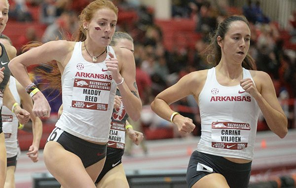 Arkansas' Carina Viljoen (from right) and Maddy Reed lead the field Saturday, Feb. 1, 2020, in the mile run during the Razorback Invitational in the Randal Tyson Track Center in Fayetteville.