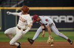 Arkansas second baseman Robert Moore misses a ground ball while a Texas runner takes second base during the first inning of a game Saturday, Feb. 29, 2020, during the Shriners Hospitals for Children College Classic at Minute Maid Park in Houston.