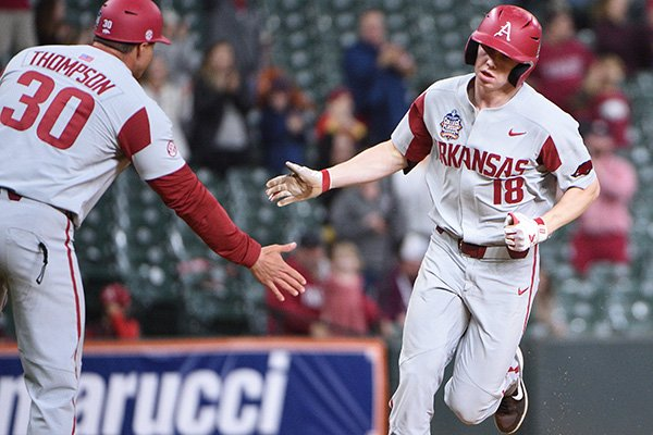 Arkansas outfielder Heston Kjerstad (18) is congratulated by hitting coach Nate Thompson after hitting a home run during a game against Texas on Saturday, Feb. 29, 2020, during the Shriners Hospitals for Children College Classic at Minute Maid Park in Houston.