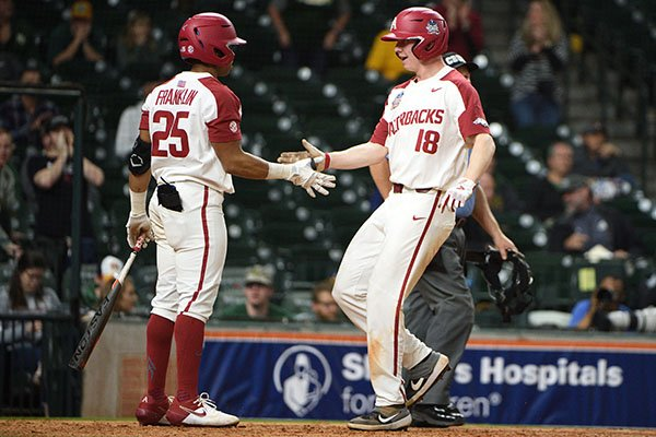 Arkansas center fielder Christian Franklin (25) congratulates right fielder Heston Kjerstad as he scores during the eighth inning of a game against Baylor on Sunday, March 1, 2020, during the Shriners Hospitals for Children College Classic at Minute Maid Park in Houston.