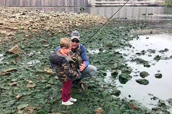 Jeremiah Gage talks with his 3-year-old son Wyatt during a recent fishing trip on the White River.