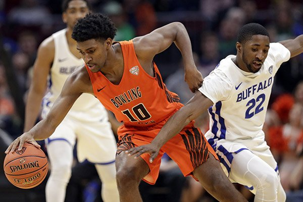 Bowling Green's Justin Turner (10) drives past Buffalo's Dontay Caruthers (22) during the second half of an NCAA college basketball championship game of the Mid-American Conference men's tournament, Saturday, March 16, 2019, in Cleveland. (AP Photo/Tony Dejak)