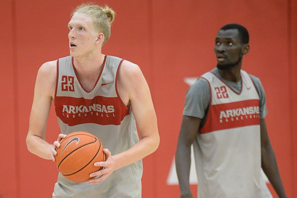 Arkansas forward Connor Vanover (23) takes a shot Thursday, Sept. 26, 2019, as forward Abayomi Iyiola walks behind during practice in the Eddie Sutton Gymnasium inside the Basketball Performance Center in Fayetteville.